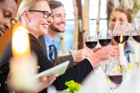 lunch: Equipo en la reuni�n almuerzo de negocios en el restaurante comiendo y bebiendo en la celebraci�n de un buen trabajo en conjunto, los alimentos y bebidas en la mesa en el fondo