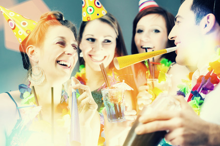 partying: Friends partying in cocktail bar with hats and music Stock Photo