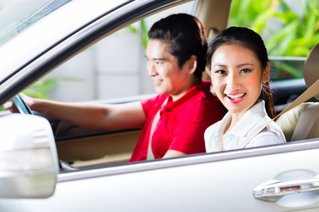 Asian couple driving new car on driveway to their home photo