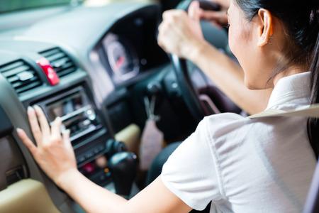 escuchando musica: Pareja asiática conducir el nuevo coche, que se está convirtiendo en la radio