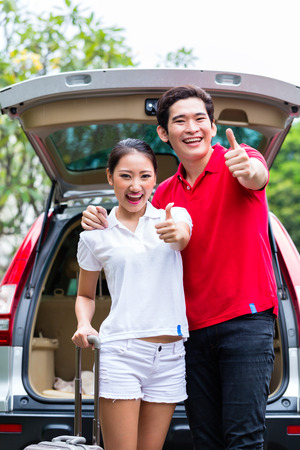 Asian couple loading suitcase for travel in luggage trunk of car photo