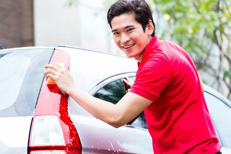 Limpieza hombre asiático y el coche lavado con esponja
