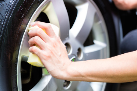 man cleaning wheel rim while car wash