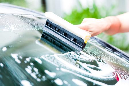 lavarse las manos: hombre parabrisas limpieza mientras lavado de coches
