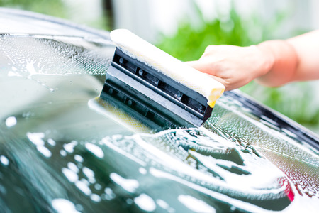 wash: man cleaning windscreen while car wash