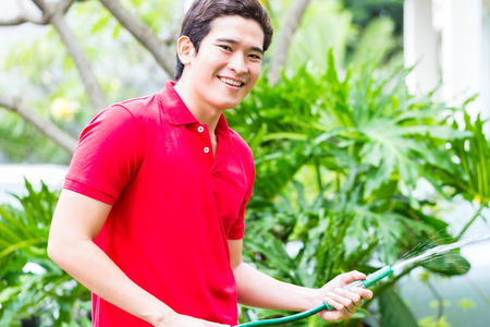 Asian man washing car or watering plants with garden hose