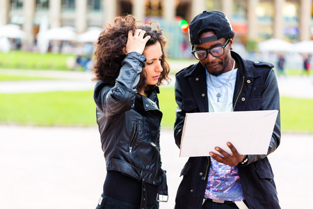 lost city: Young African American couple getting lost doing sightseeing with city map Stock Photo