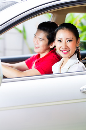 korean man: Asian couple driving new car on driveway to their home