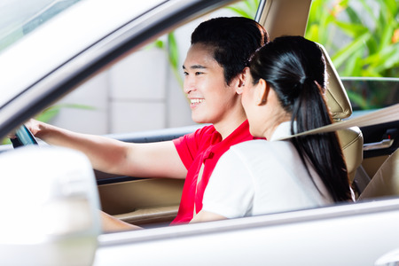 driveway: Asian couple driving new car on driveway to their home