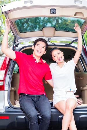 Asian couple buying new car, cheering and sitting in luggage trunk photo