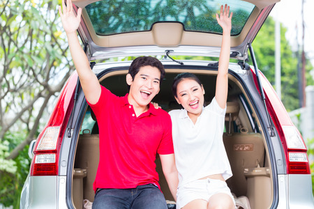 couple outdoor: Asian couple buying new car, cheering and sitting in luggage trunk