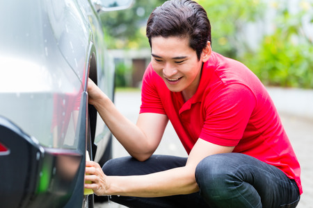 rims: Asian man cleaning car rims with sponge Stock Photo