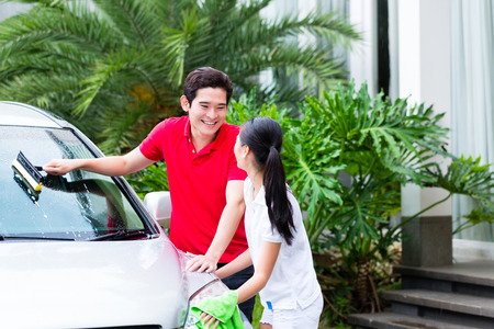 washing car: Asian couple cleaning windscreen or windshield and headlamps while car wash Stock Photo