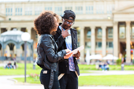north american: Young African American couple doing sightseeing with city map Stock Photo