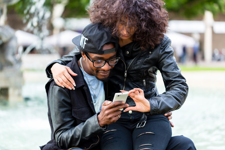 african american: African American man sitting with girlfriend at fountain showing message on mobile phone or looking up information