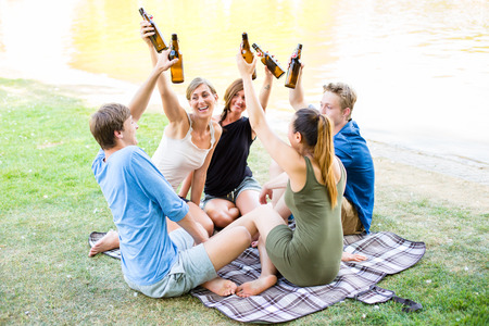 beer after work: Students in park toasting with beer bottles having picnic at river Stock Photo