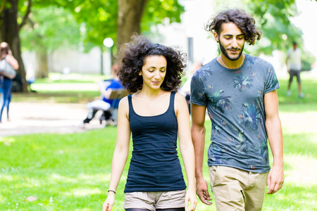 latin man: Couple, Latin man and woman, walking holding hands over meadow Stock Photo