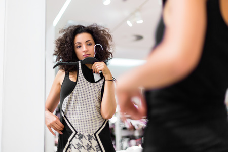 Woman shopping fashion, trying on dress in store photo