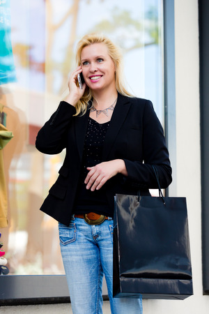 telephoning: Mature woman with bags shopping in city using phone in front of shop window