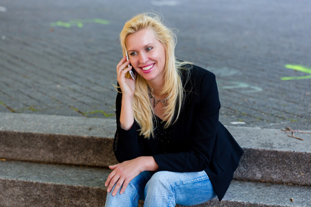 telephoning: Mature woman telephoning with smartphone in city Stock Photo