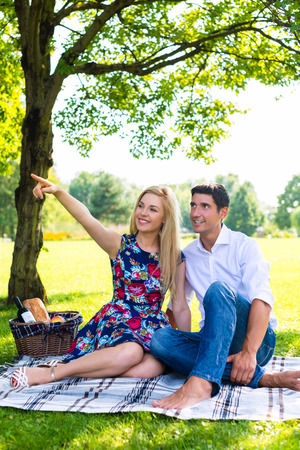 picnic blanket: Couple, man and woman, having picnic on summer meadow Stock Photo