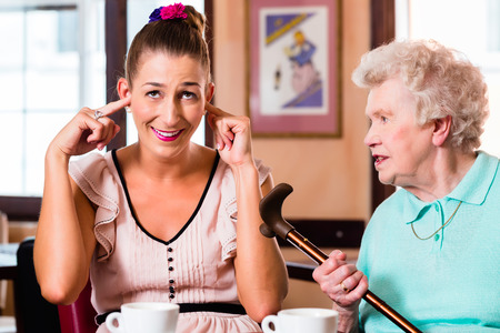 Grandmother and granddaughter having argument in cafe, the young woman is closing her ears photo