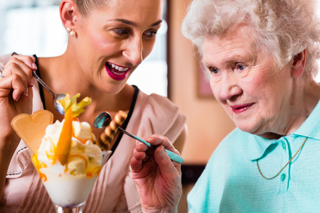 old people eating: Senior woman and granddaughter having fun eating ice cream sundae in cafe Stock Photo