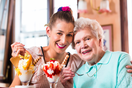 ice cream woman: Senior woman and granddaughter having fun eating ice cream sundae in cafe Stock Photo