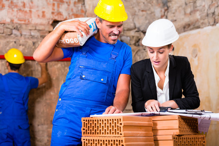 Architect and construction worker having sack of cement on shoulder on site with plan photo