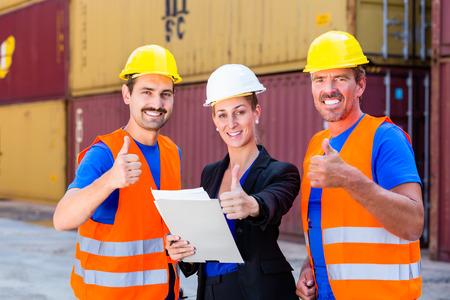 empleadas domesticas: Dos trabajadores y el gerente de la empresa de envío en discusiones sobre documentos de transporte o de envío Foto de archivo