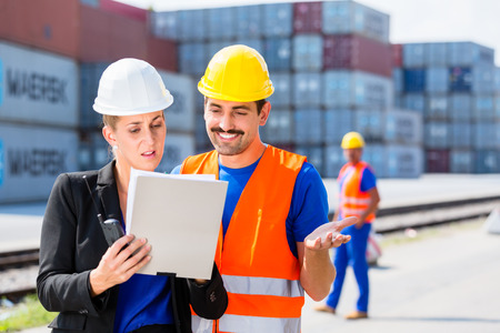 Manager with clipboard full of freight documents talking with worker on shipment yard in front of container Stock Photo