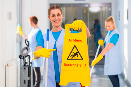 cleaning crew: Cleaning lady showing warning sign because the floor is wet and there is danger of accidents Stock Photo