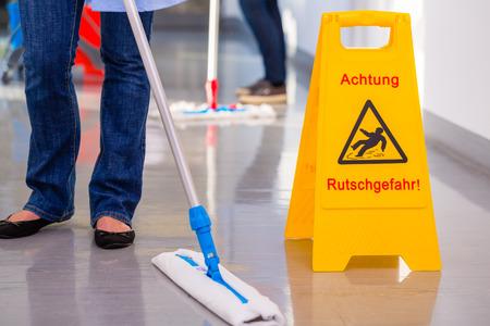 personal de limpieza: Señal de peligro en frente de la tripulación de la limpieza, el suelo está mojado y no hay peligro de accidentes