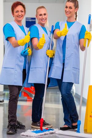 cleaning team: Se�oras de la limpieza que trabajan en equipo mostrando los pulgares para arriba signo