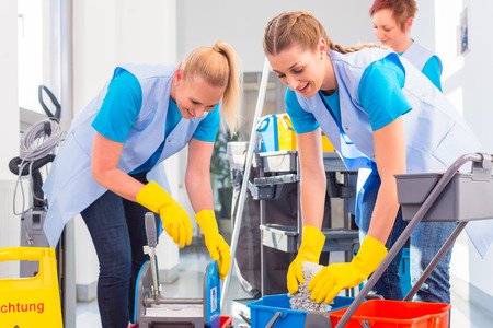 Commercial cleaners doing the job together, three women with trolley working