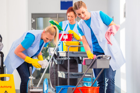 charlady: Commercial cleaners doing the job together, three women with trolley working