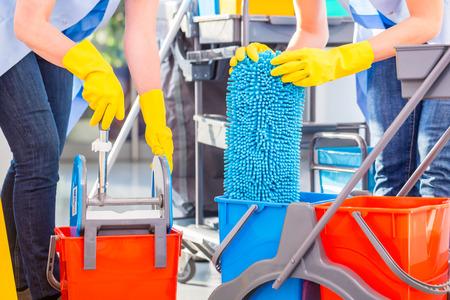 anuncio publicitario: Se�oras de la limpieza de remanentes piso, cerca de las manos y herramientas