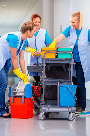 charwoman: Commercial cleaning brigade working in corridor Stock Photo