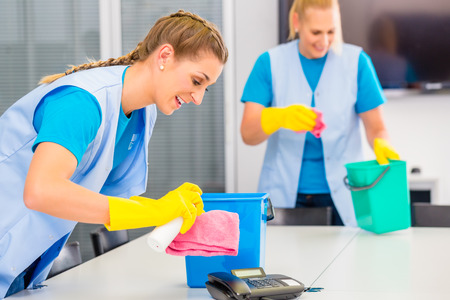 cleaning crew: Commercial cleaning crew ladies working as team in office