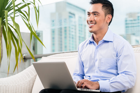 indonesian people: Businessman working with laptop from home being a telecommuter