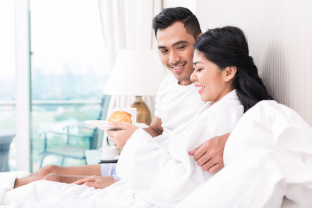 lounging: Asian couple lounging in bed at morning Stock Photo
