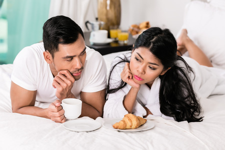 lying on bed: Marital issues - asian man feeling rejected by his wife, they are laying in bed