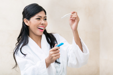 Asian woman being joyfully checking her pregnancy test in the morning photo