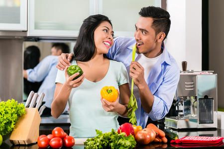 Asian couple, man and woman, cooking food together in kitchen preparing dinner photo