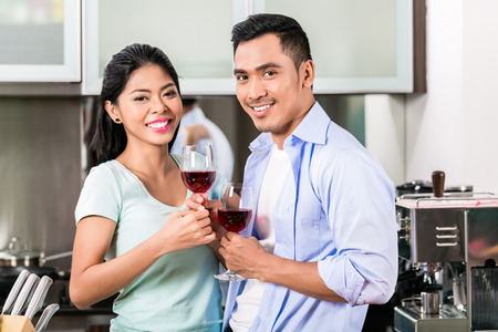 Asian couple, man and woman, drinking red wine in kitchen photo