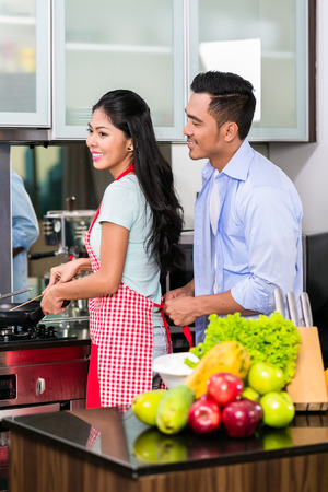 asian wife: Couple in domestic Kitchen cooking food Stock Photo