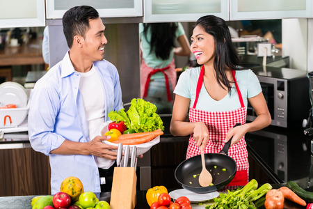 Asian man and woman cooking together in kitchen preparing dinner