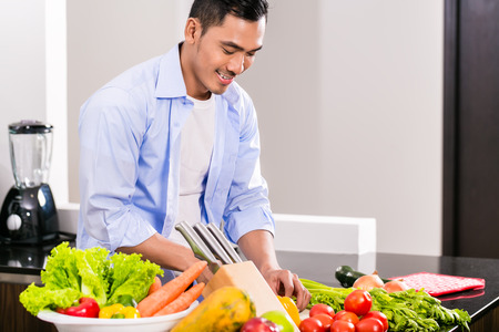 Asian man cutting vegetables and salad in kitchen