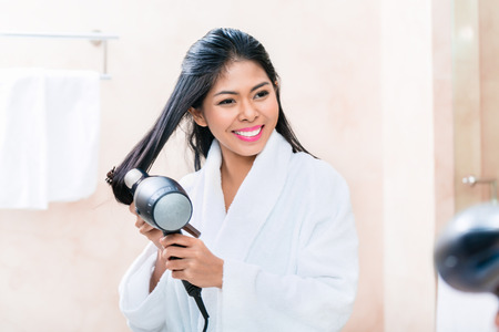 southeast asia: Asian woman in bathroom drying hair with blow dryer