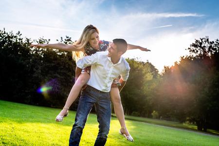 carrying girl: Man carrying girl piggyback in summer in backlit sunset scene Stock Photo